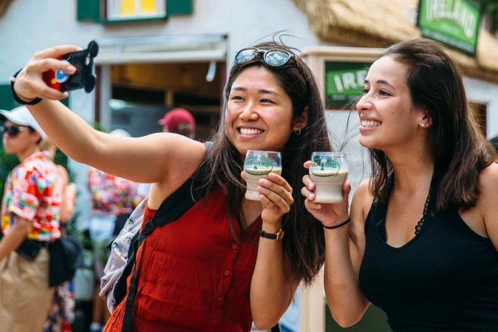 Photo of 2 women outside the Ireland food kiosk at Epcot taking a selfie with a drink.