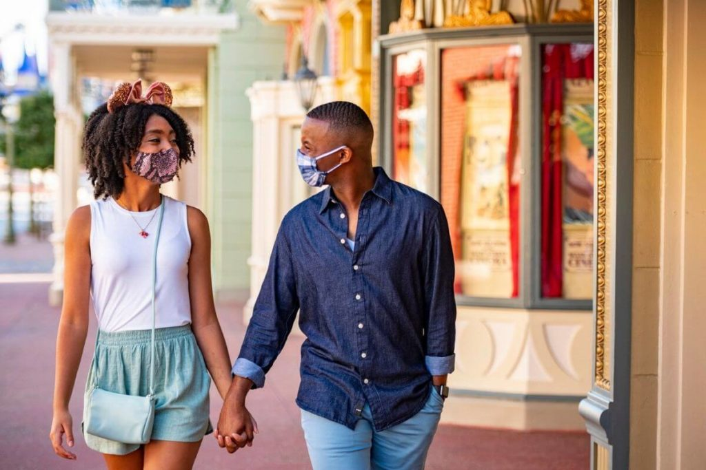Close up of a couple a Disney World, holding hands while looking at each other adoringly.