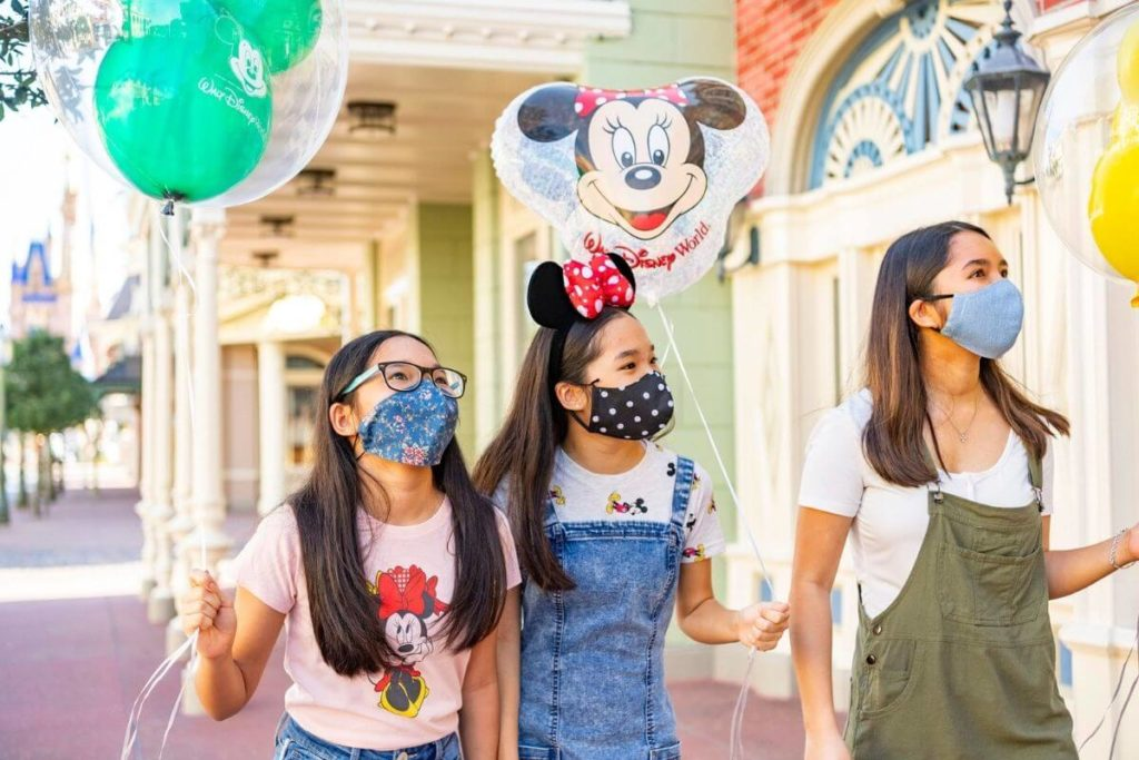 Photo of a woman and 2 children wearing protective face masks while at Disney World.