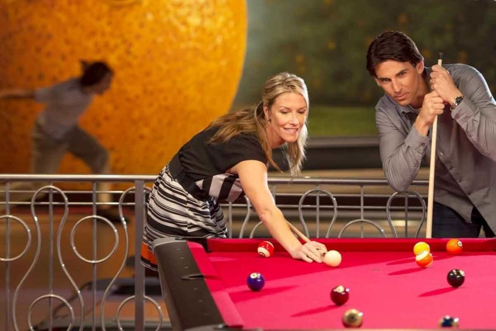 Photo of a man and woman playing pool while a person bowls in the background.