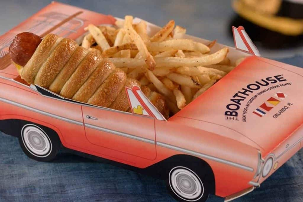 Closeup photo of a hot dog wrapped in a croissant and french fries nestled in a cardboard container shaped like a pink convertible.