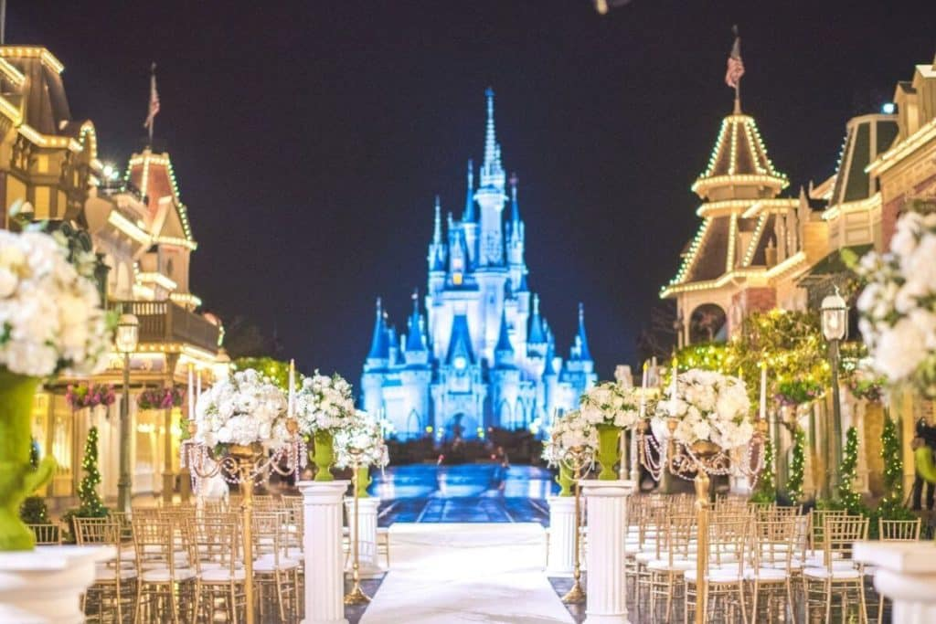 Photo of seating and decor set up for a wedding ceremony with Magic Kingdom's Cinderella's Castle in the background.