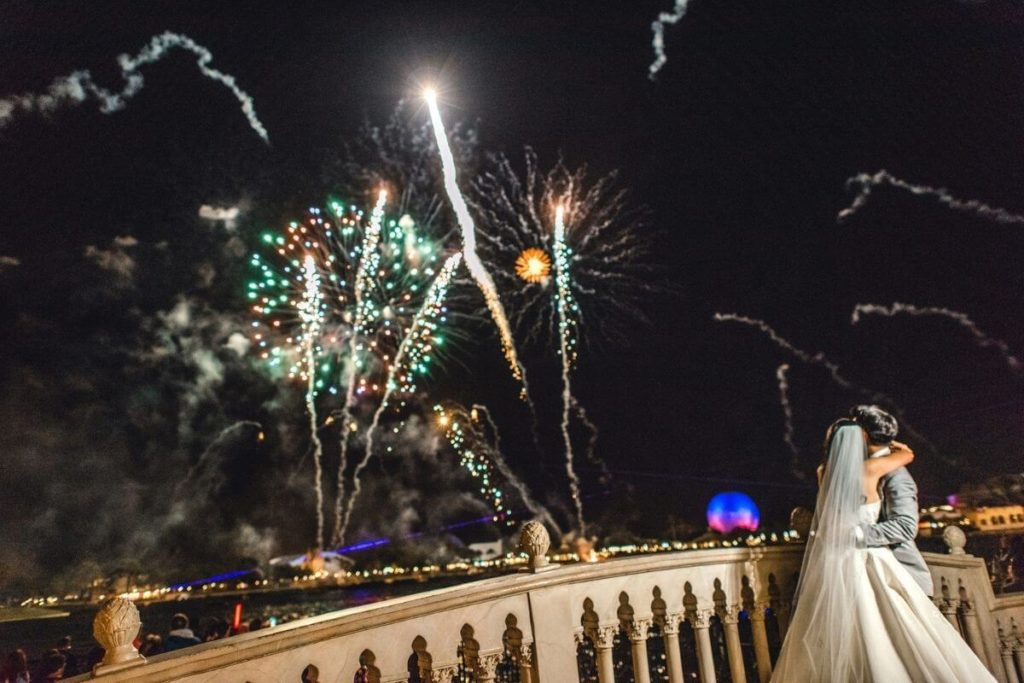 Closeup of a bride and groom embracing while watching Epcot's nighttime show, Epcot Forever.