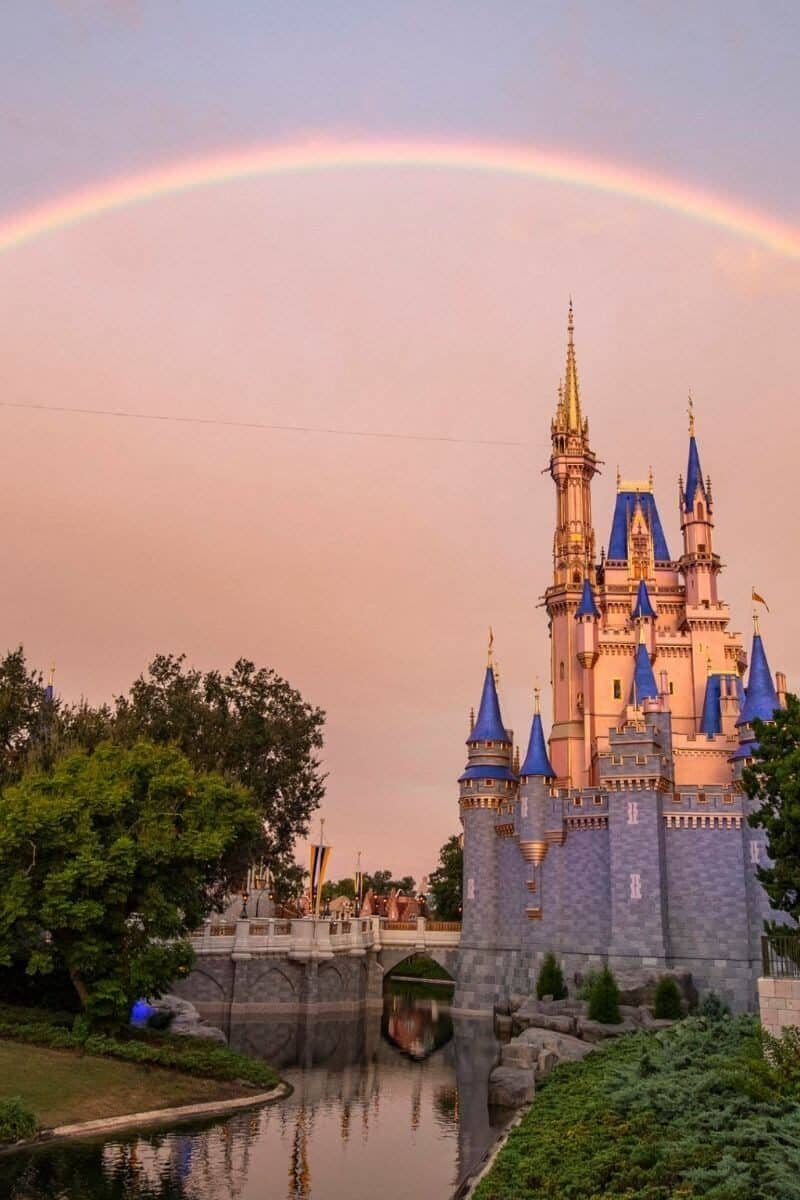Photo of Cinderella's Castle with grey skies and a rainbow over the castle.