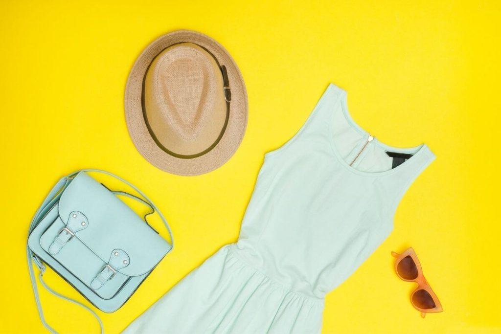 Flat lay photo of a mint handbag, straw hat, coral sunglasses, and a mint jersey tank dress.