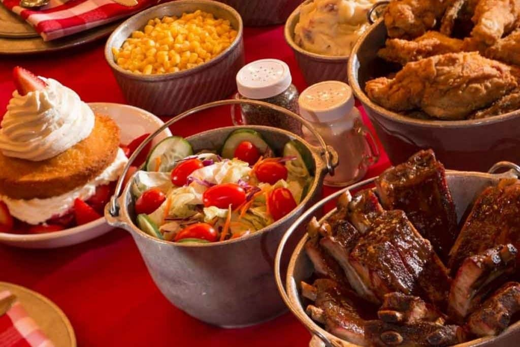 Closeup photo of a table with buckets and bowls full of barbecue foods.