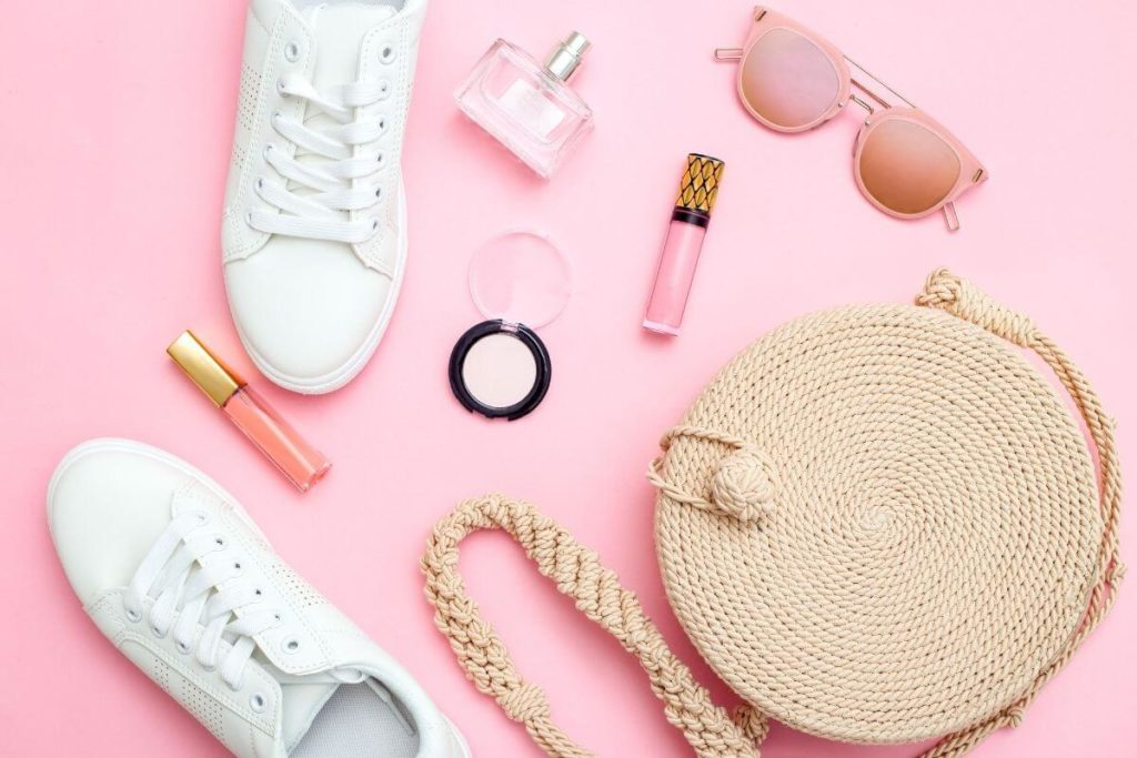Flat lay photo of a straw purse, white sneakers, pink lip gloss, pink eyeshadow, perfume, and pink sunglasses.