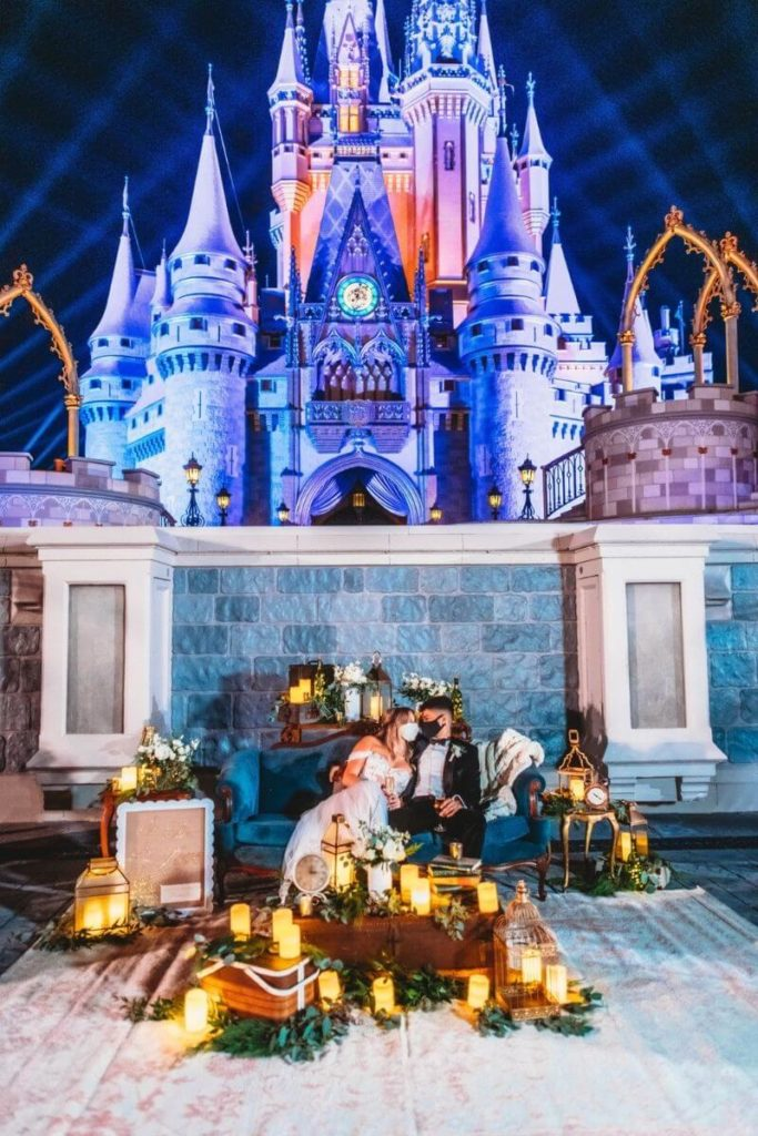 A couple poses in an elaborate settee at the foot of Cinderella's castle at Disney World's Magic Kingdom.