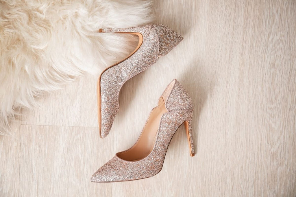 Photo of silver glittery high heels laying on a faux fur rug and wooden floor.