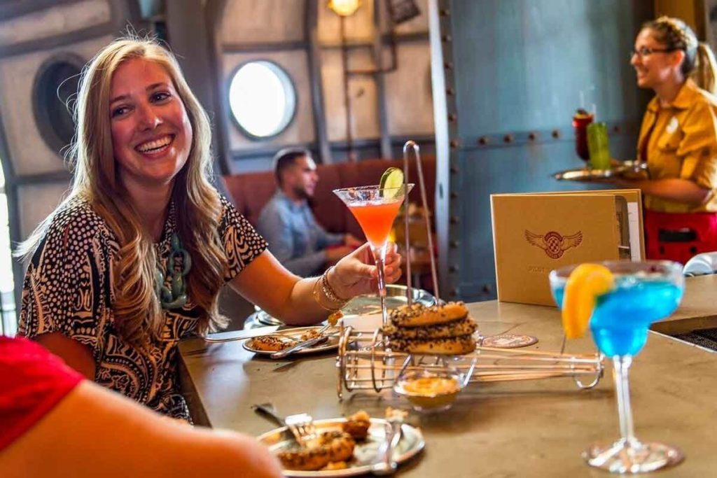 Photo of a woman holding a red cocktail while talking to someone with a server in the background holding a tray of drinks.