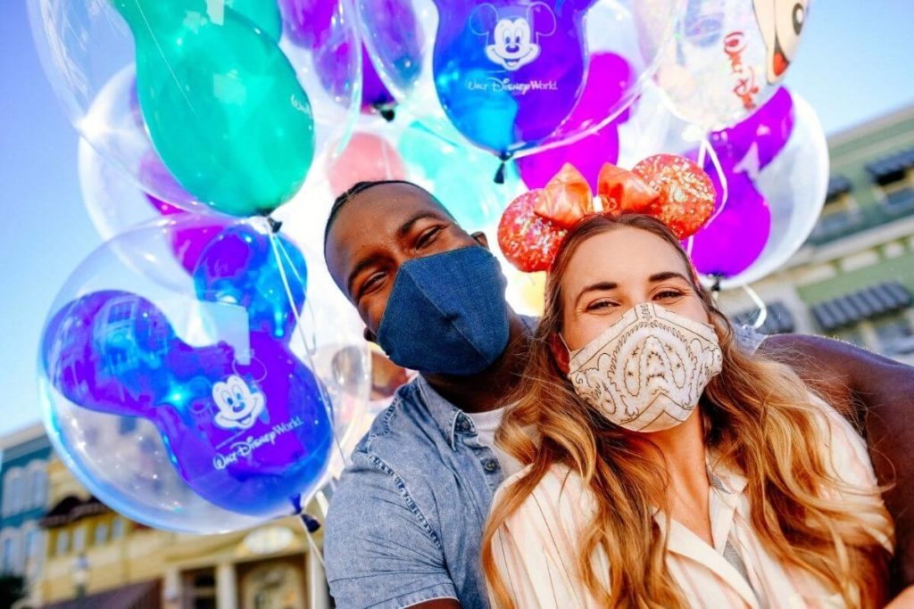 Photo of a man and woman posing with a group of balloons.