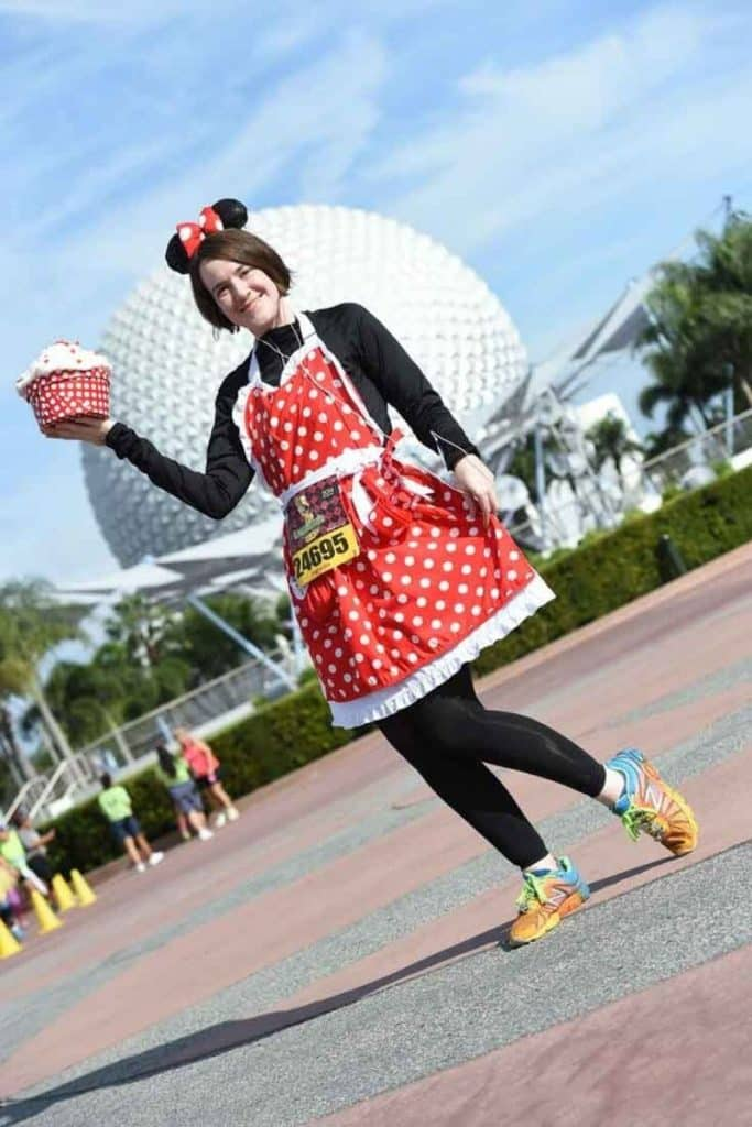 Photo of a woman in running gear with a Minnie Mouse themed apron with the Epcot ball in the background.
