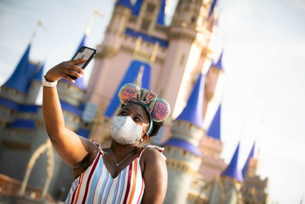 Photo of a young woman taking a selfie in front of Cinderella's Castle at Magic Kingdom.