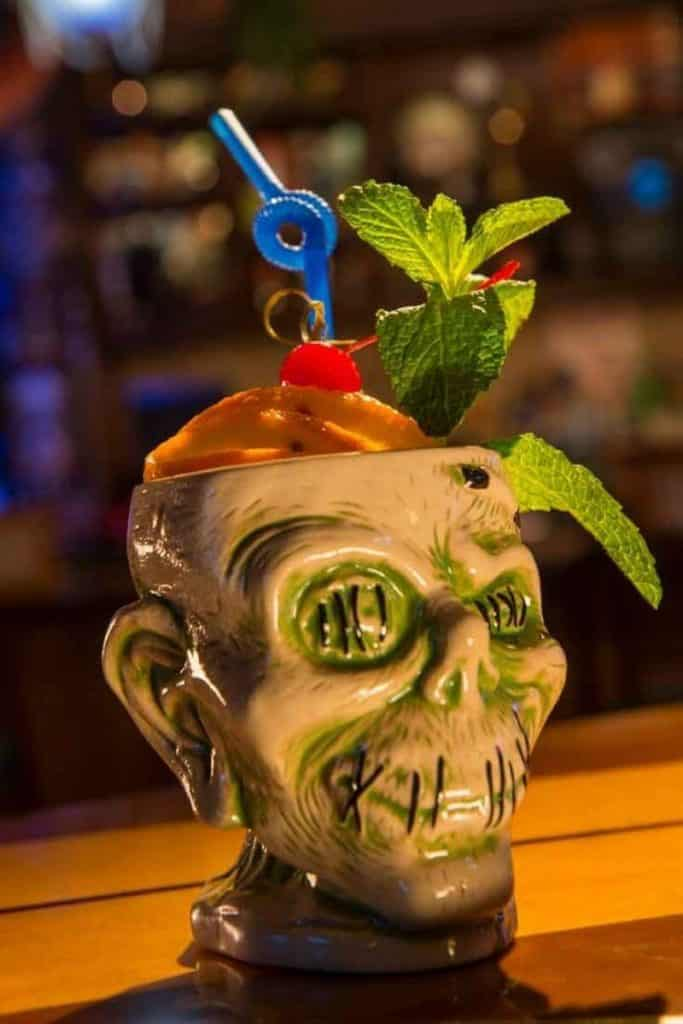 Closeup of a ceramic zombie shaped cup with fruit and a straw poking out the top.