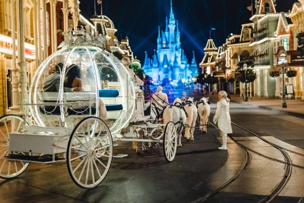 Photo of a bride and groom in a fancy horse-drawn carriage at the start of Main Street in Disney World's Magic Kingdom with Cinderella's castle light up in blue.
