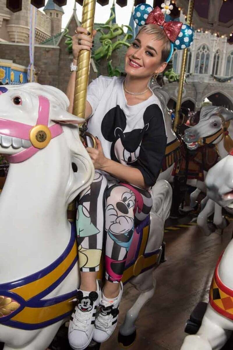 Photo of celebrity Katy Perry riding the carousel at Disney World.