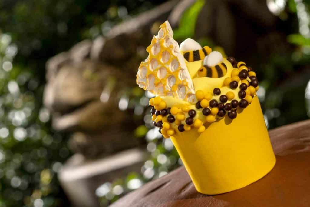 Closeup of a cupcake with yellow frosting, a candy honeycomb, candy bumblebees, and yellow and black candy pearls on top from Disney World's Animal Kingdom.