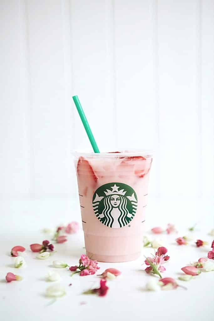 Photo of the pink drink with strawberries from Starbucks with pink and white flower buds artfully arranged around it.