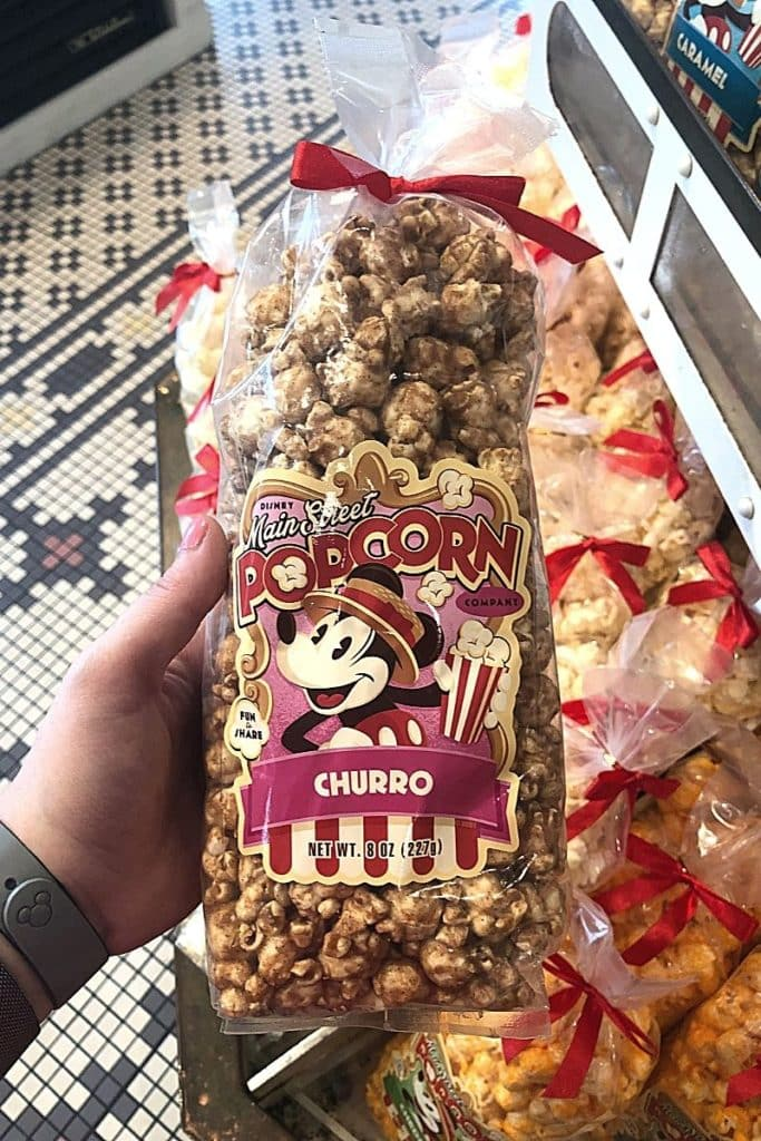 Closeup of a person holding a bag of churro flavored popcorn from Main Street Bakery.