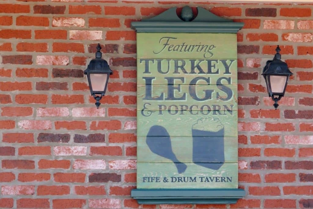"""Closeup of a sign that reads """"Featuring Turkey Legs & Popcorn: Fife & Drum Tavern."""""""