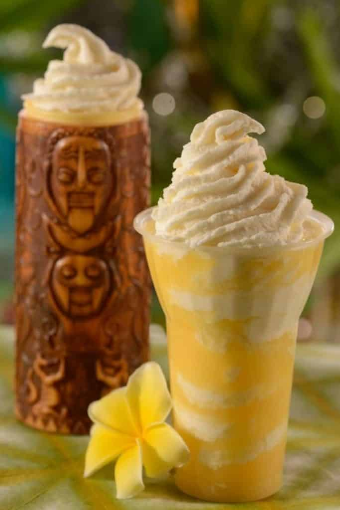 Photo of a pineapple DOLE Whip float and a wooden tiki glass with whipped cream at the top.