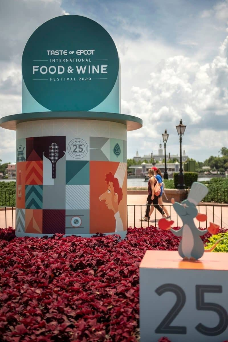 Closeup of the Taste of Epcot Food & Wine Festival sign inside the Epcot theme park with artwork depicting characters from Ratatouille.
