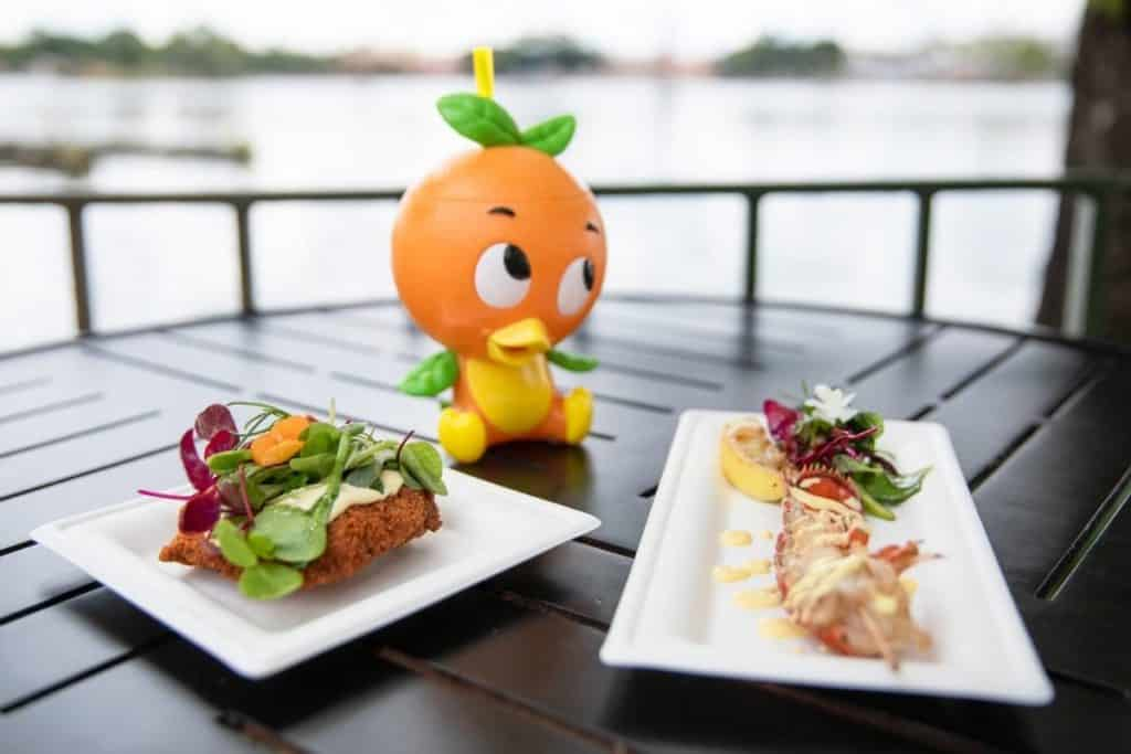 Photo of options from the Citrus Blossom marketplace at the Epcot Food & Wine Festival: crispy citrus chicken, orange bird sipper cup with an orange cream shake, and a lobster tail with meyer lemon emulsion.