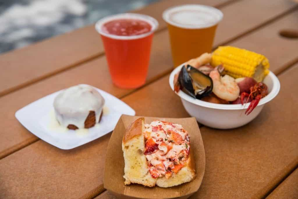 Photo of food options on a picnic table at the Epcot Food and Wine Festival: carrot cake, New England lobster roll, Southern seafood boil, and 2 craft beer selections.