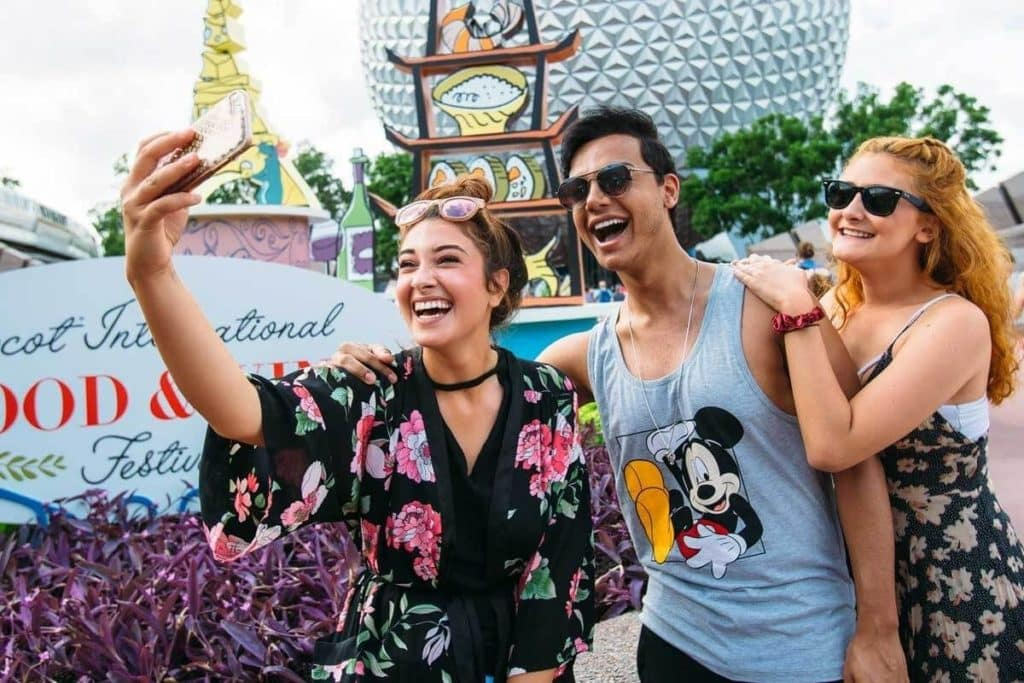 Photo of 3 young adults taking a selfie in front of the Epcot Food and Wine Festival sign.