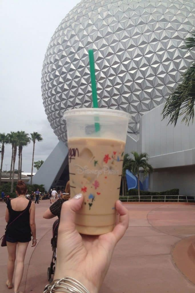 Closeup of a venti iced coffee from Starbucks at Epcot with the Epcot ball in the background