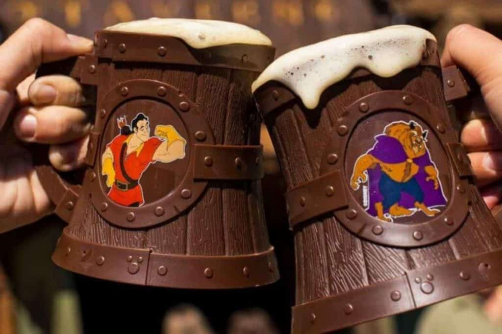 Closeup of 2 people clinking souvenir mugs filled with Lefou's Brew at Disney World's Magic Kingdom.