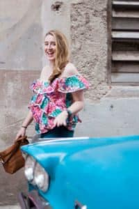 Photo of Meg Frost in Havana, Cuba wearing a brightly colored shirt behind a sky blue retro car.