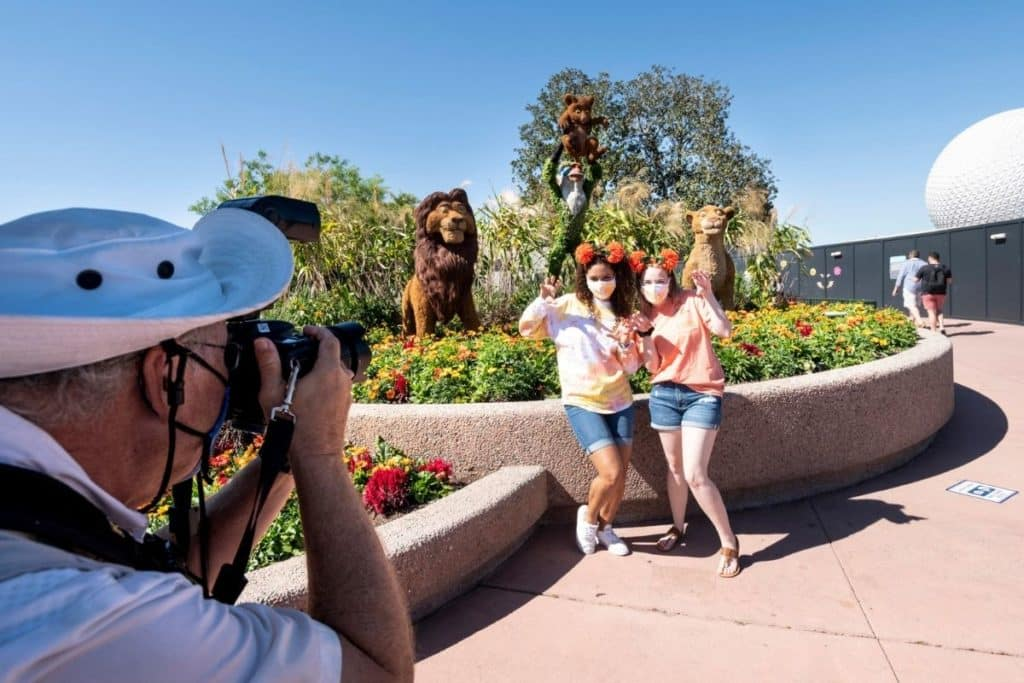 Two young women pose in front of Lion King themed topiaries while a Disney World photographer takes their picture.