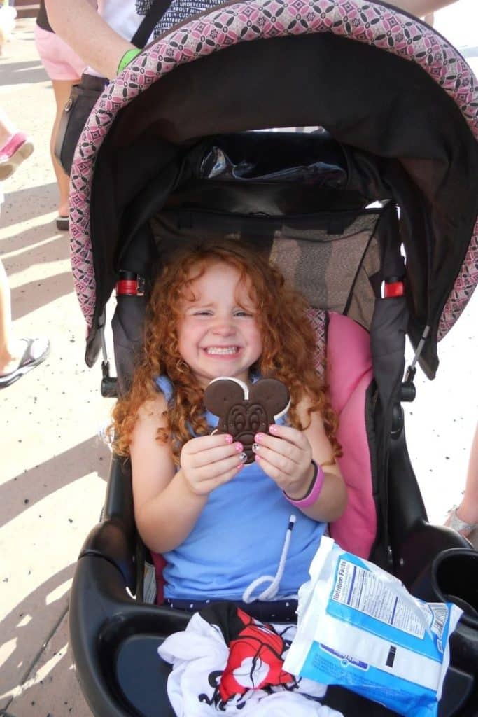 Photo of a young girl smiling in a stroller while holding a Mickey ice cream sandwich, a classic ice cream treat at Disney World.