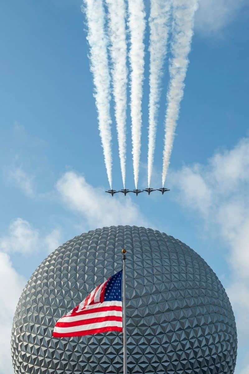 Photo of 5 military jets flying over Spaceship Earth with the American flag in the front at Disney World's Epcot.
