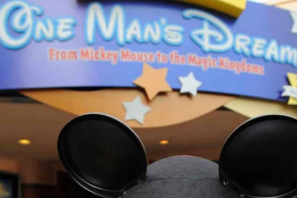 Closeup of a person wearing a Mickey Mouse ear hat in front of the entrance to One Man's Dream at Disney World's Hollywood Studios.