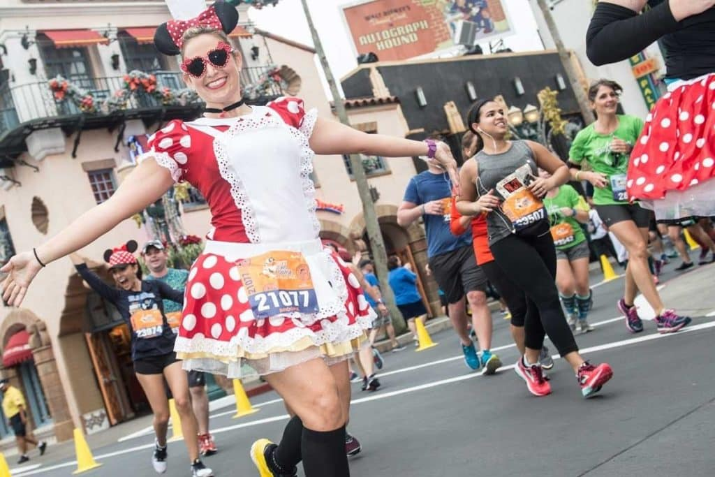 Photo of a woman running in a Minnie Mouse costume at a RunDisney race at Disney World.