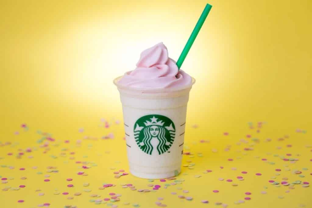 Closeup of a pink strawberry frappucino against a bright yellow background.