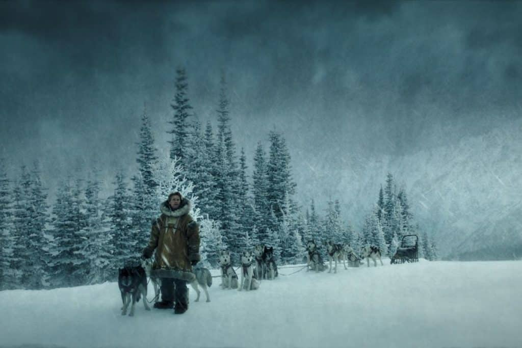 Screenshot with a man and about a dozen sled dogs in the snow from one of many dog movies on Disney Plus, Togo.