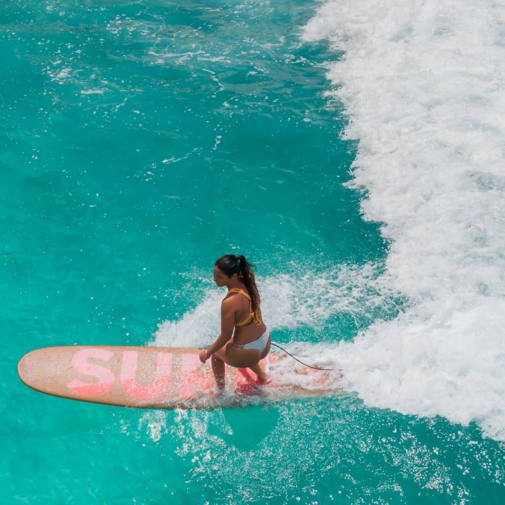 Aerial photo of a woman surfing in turquoise waters.