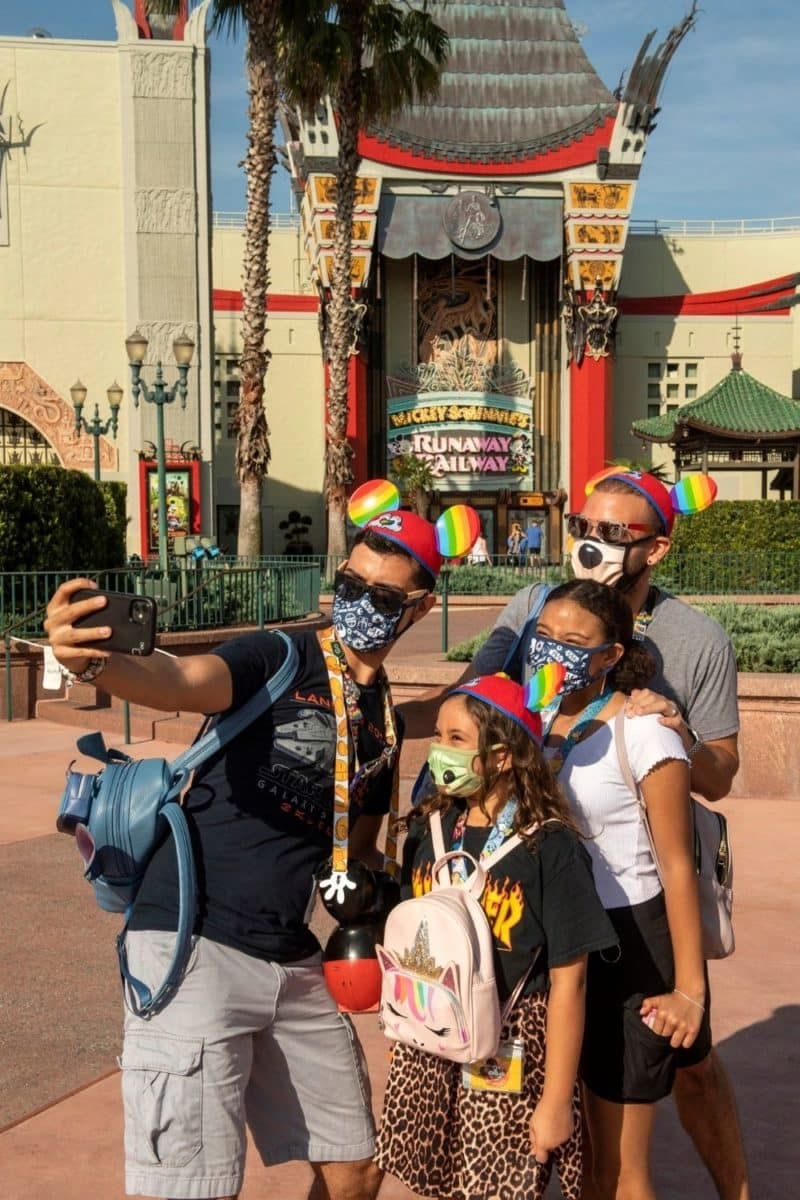 Photo of 2 dads with their 2 daughters taking an Instagram photo in front of Mickey & Minnie's Runaway Railway at Disney World's Hollywood Studios.
