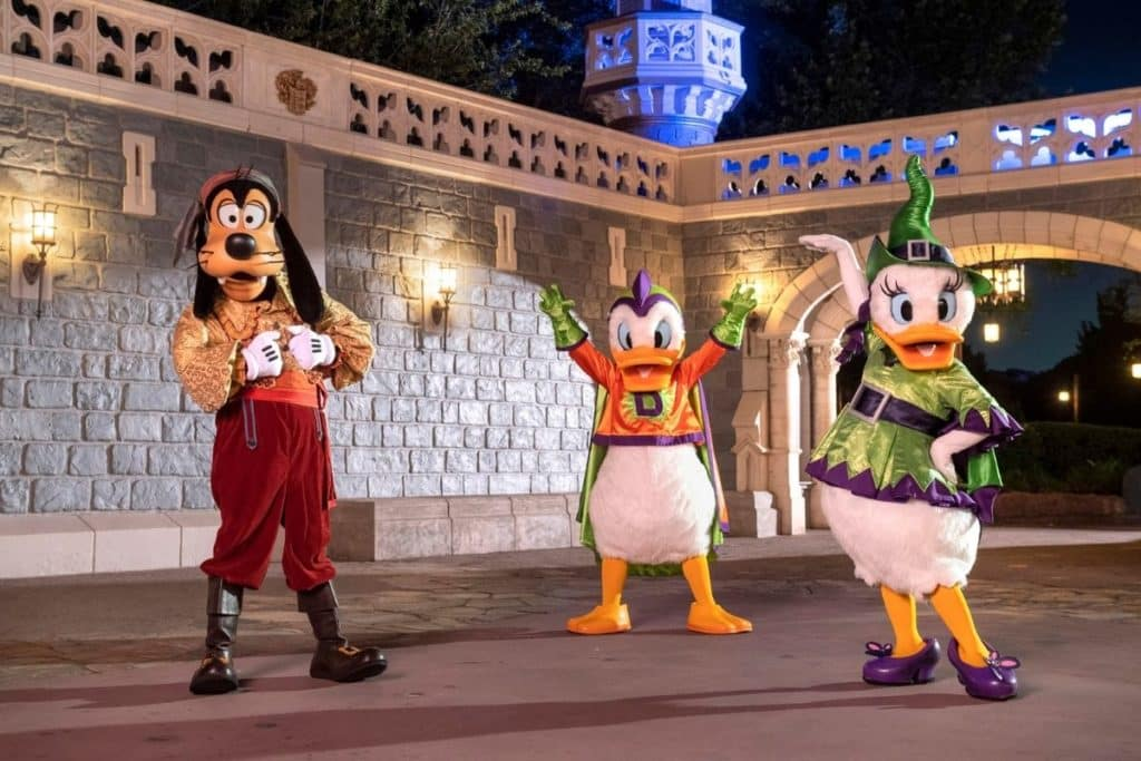 Photo of Goofy, Donald Duck, and Daisy Duck posing at Magic Kingdom while wearing Halloween costumes.