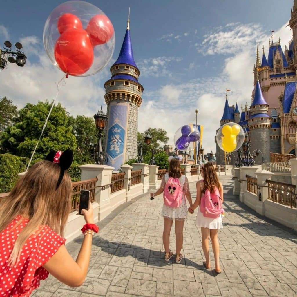 Photo of a young girl taking an Instagram photo of her 2 friends walking toward Cinderella's Castle at Disney World with Mickey balloons in their hands.