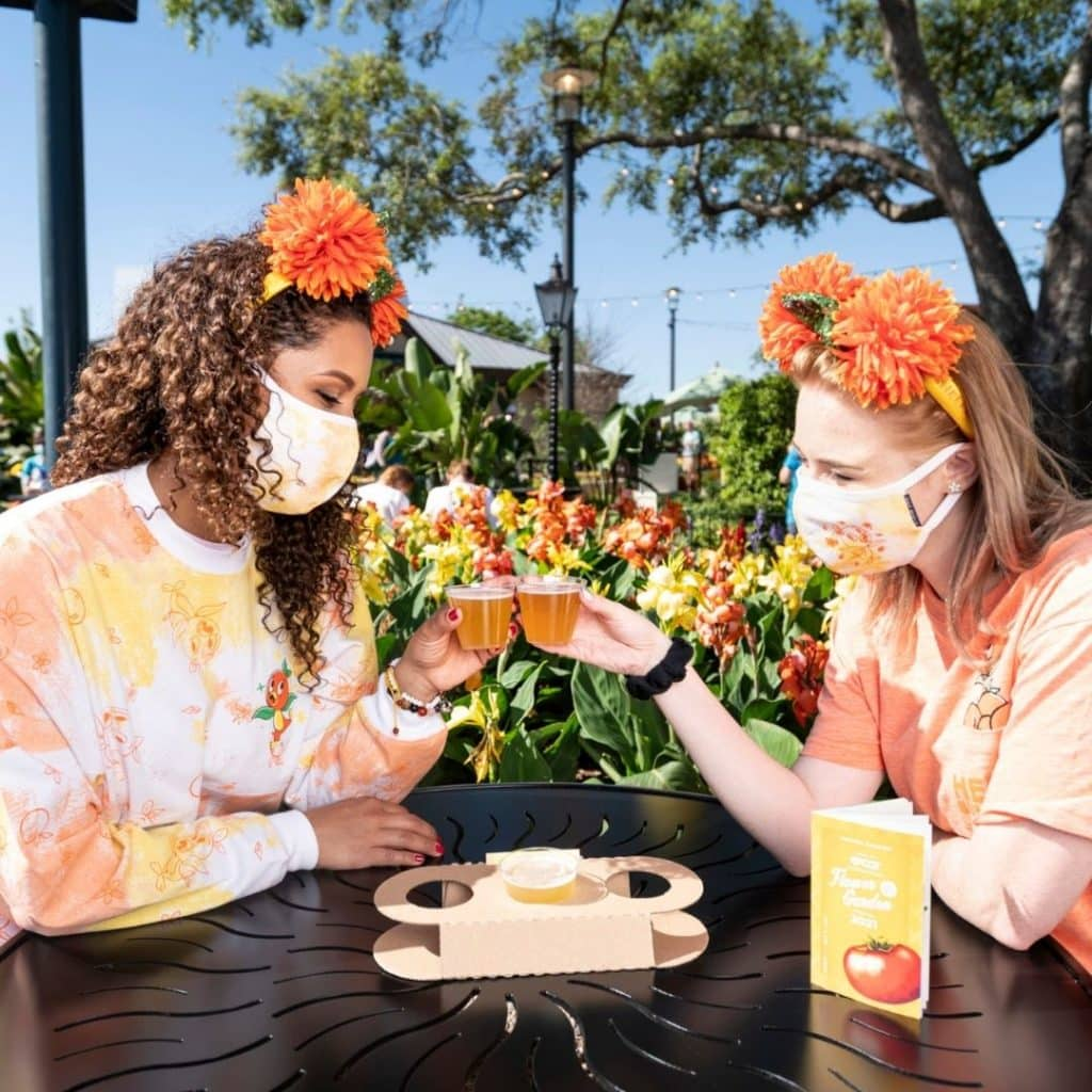 Photo of 2 women at the Epcot Flower & Garden Festival clinking beer samples.