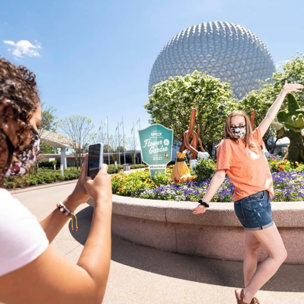 Photo of a woman taking an Instagram photo of her friend posing in front of the iconic Epcot sphere.