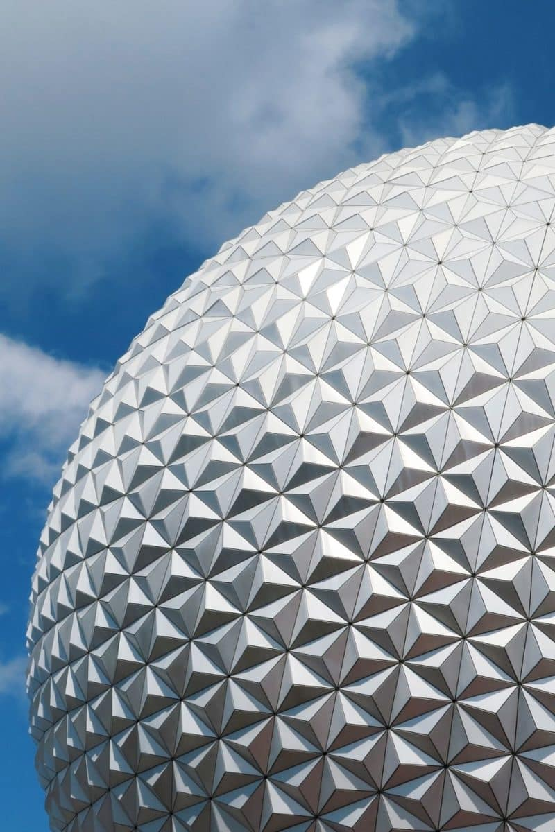 Closeup of the Epcot ball during the day set amidst cloudy skies.