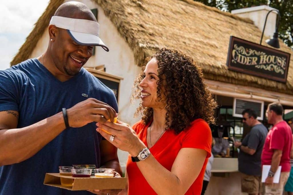 Photo of a couple sampling alcoholic cider from Cider House at the Epcot Food & Wine Festival.