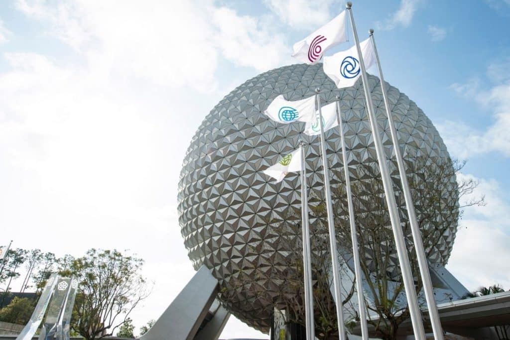 Photo of Spaceship Earth with the new World flags flying in front of it.