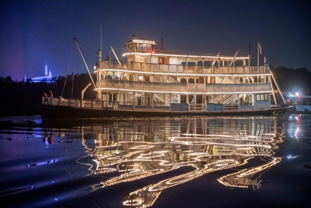 Photo of the Liberty Belle paddleboat ride all lit up at night, reflecting in the lake.