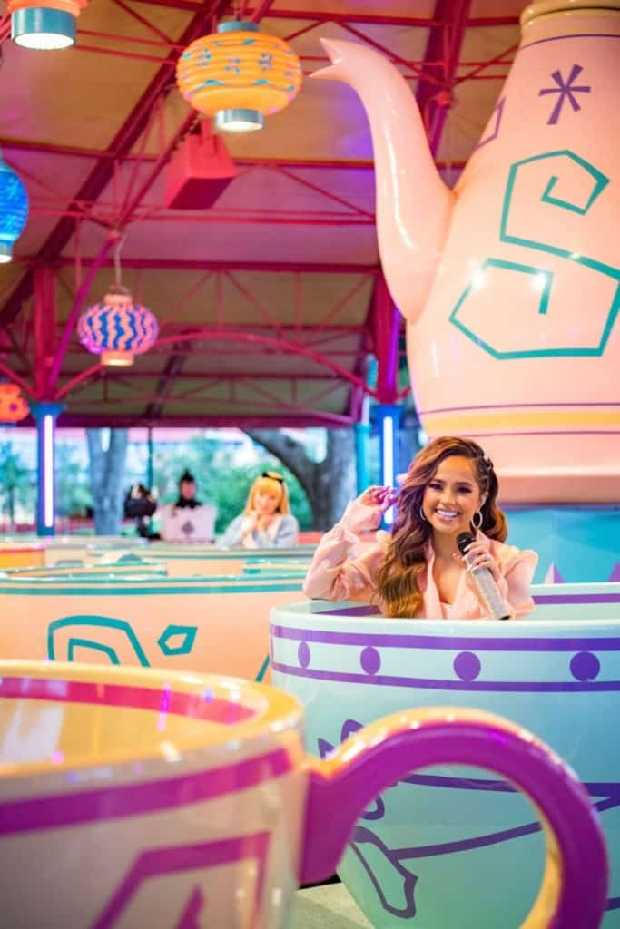 Photo of singer Becky G riding Mad Tea Party ride at Magic Kingdom with Alice in the background.